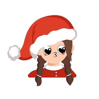 Девушка с большими сердечными глазами и поцелуем в губы в красной шляпе санты. милый ребенок с любящим лицом в карнавальном костюме на новый год, рождество и праздник. голова очаровательного ребенка