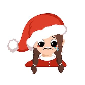 울고 눈물 감정, 슬픈 얼굴, 빨간 산타 모자에 우울한 눈을 가진 소녀. 새해, 크리스마스, 휴일을 위한 카니발 의상을 입은 우울한 표정을 가진 귀여운 아이. 사랑스러운 아이의 머리