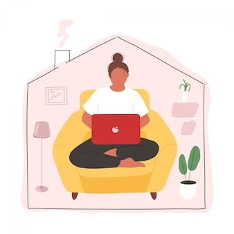 Girl with laptop working from home in armchair
