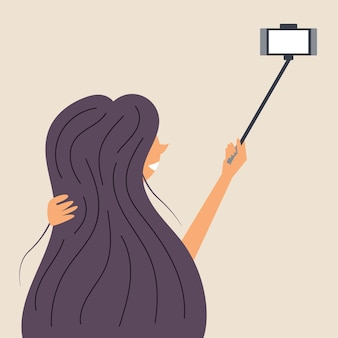 A girl with long hair is photographed on a selfie stick