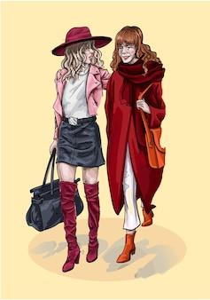 Подружки идут по улице в модных нарядах.
