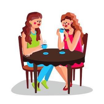 Девушки пьют горячий кофе за столом в кафе