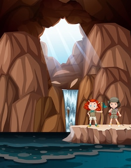 Girls exploring a cave with waterfall