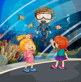 Girls looking at fish and diver in the aquarium