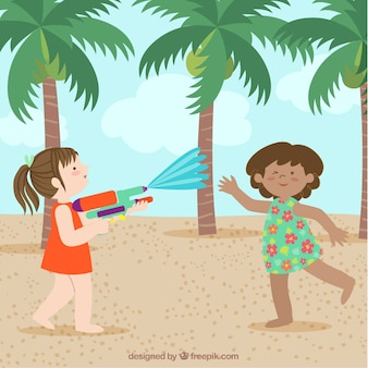 Girls playing with water guns in the beach