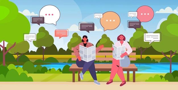 Девушки читают газету, обсуждают ежедневные новости во время встречи в концепции общения пузыря чата парка. женщины сидят на деревянной скамейке пейзажный фон полная длина по горизонтали