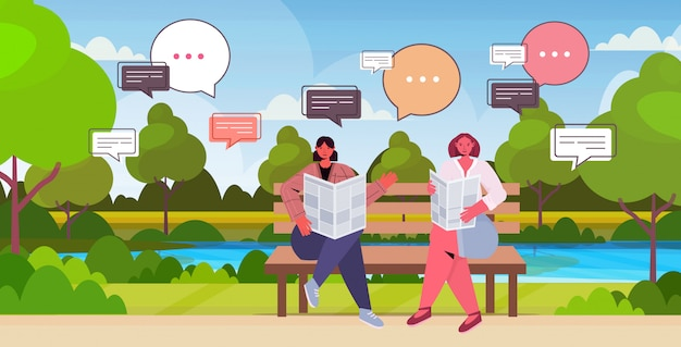 Girls reading newspaper discussing daily news during meeting in park chat bubble communication concept. women sitting on wooden bench landscape background full length horizontal
