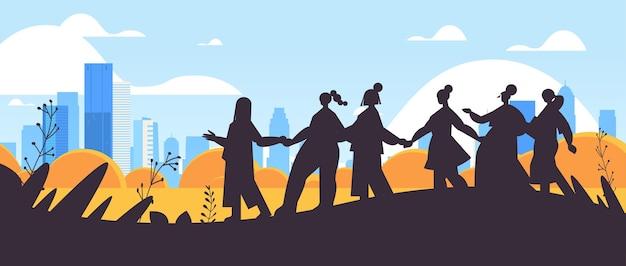一緒に立っている女の子のシルエット女性のエンパワーメント運動フェミニストの女性のコミュニティ連合コンセプト都市景観背景水平全長ベクトルイラスト