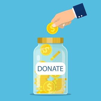 Стеклянная банка для пожертвований и монеты в руке