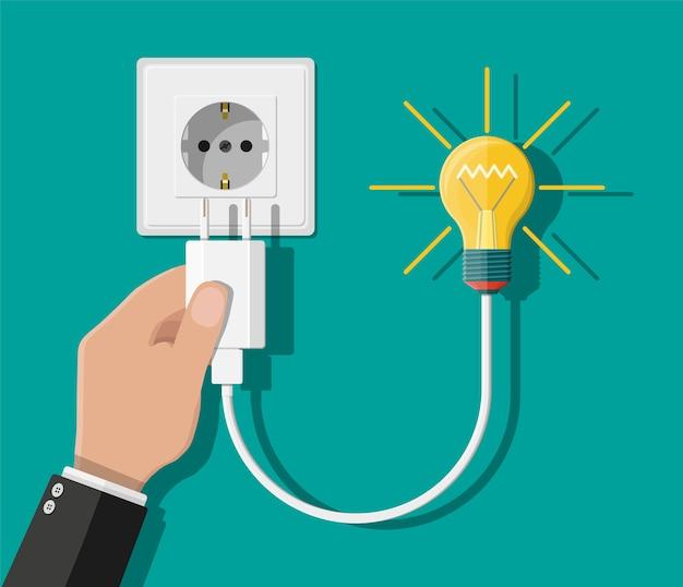 Стеклянная лампочка. вилка шнура питания подключена к розетке. концепция творческой идеи или вдохновения. стеклянная колба со спиралью в руке в плоском стиле. векторная иллюстрация