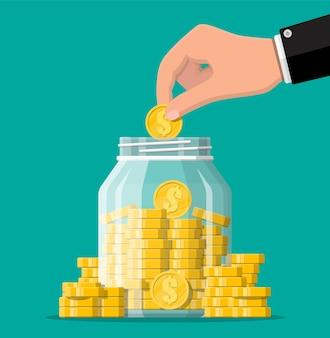 금화와 손의 전체 유리 돈 항아리. moneybox에 달러 동전을 저장합니다. 성장, 소득, 저축, 투자