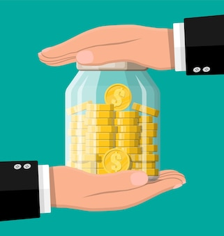 Стеклянная банка для денег, полная золотых монет и рук. сохранение долларовой монеты в копилке