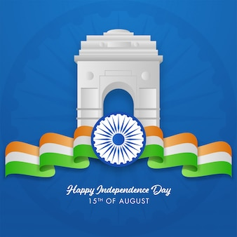 Glossy india gate with ashoka wheel and wavy tricolor ribbon on blue background , happy independence day.