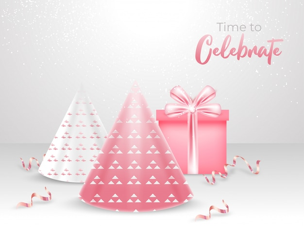 Glossy party hats and gift box on white