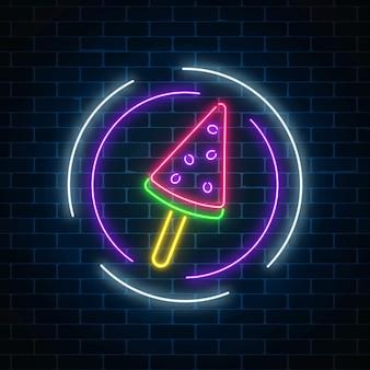 Glowing neon ice cream cafe signboard on dark brick wall background. watermelon ice-cream lolly.