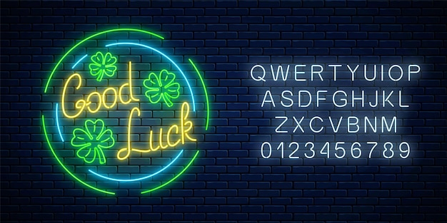 Glowing neon sign with geed luck wish and four-leaf clovers in circle frames with alphabet on dark brick wall background. hand drawn lettering and three leaves of shamrock. vector illustration.