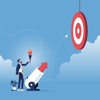 目標達成コンセプト-ビジネスマンが大砲を通してビジネスの矢を発射