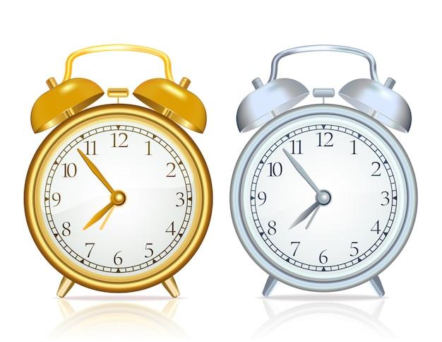 ゴールドの目覚まし時計と白い背景の上の銀の目覚まし時計