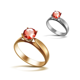 Золотые и серебряные обручальные кольца с красным блестящим прозрачным бриллиантом крупным планом на белом