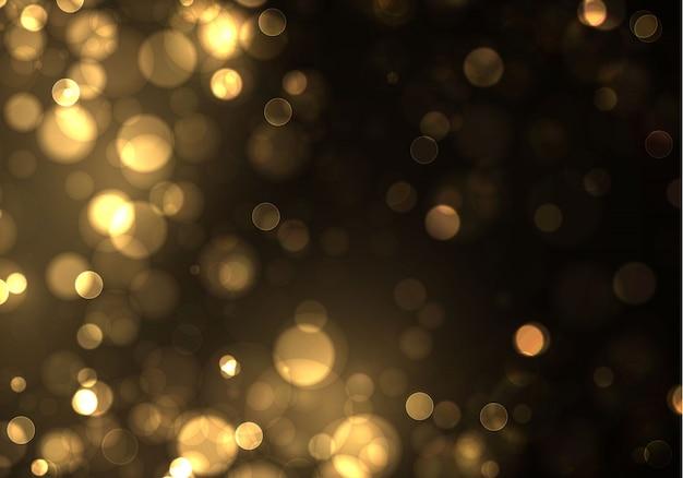 ゴールドのボケは黒い背景にぼやけた光。黄金色のライトと年末年始のテンプレート。抽象的なキラキラデフォーカス点滅星と火花。