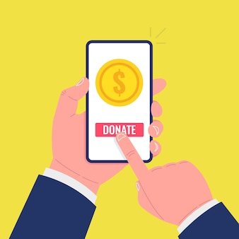 Gold coin and donate button on smartphone screen. hand holds smartphone, finger touches screen.