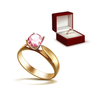 Gold engagement ring with pink shiny clear diamond in red jewelry box close up isolated on white background