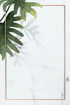 흰색 대리석 배경에 philodendron radiatum 잎 패턴이 있는 골드 프레임