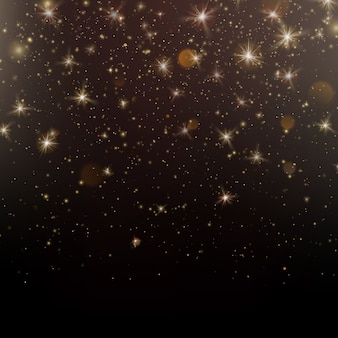 Gold glittering star dust sparkling particles on dark background.
