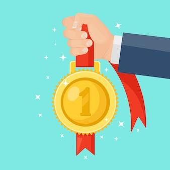 손에 첫 번째 장소에 빨간 리본으로 금메달. 트로피, 배경에 우승자 상. 황금 배지 아이콘입니다. 스포츠, 사업 성과, 승리.