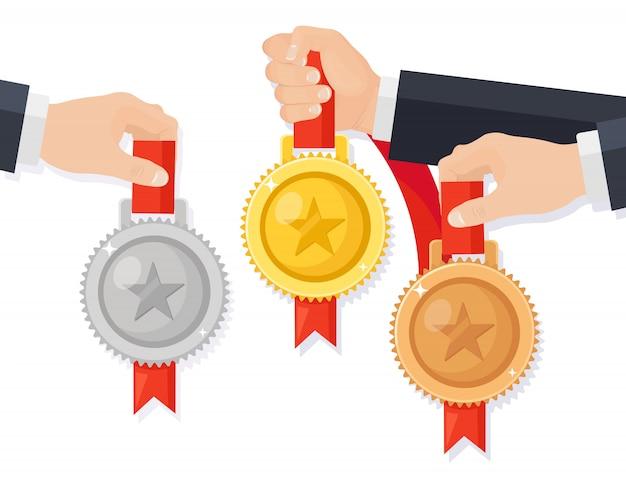 ゴールド、シルバー、ブロンズメダルを手元に。トロフィー、背景に分離された勝者のための賞。リボンとゴールデンバッジのセットです。達成、勝利。漫画イラストフラットデザイン
