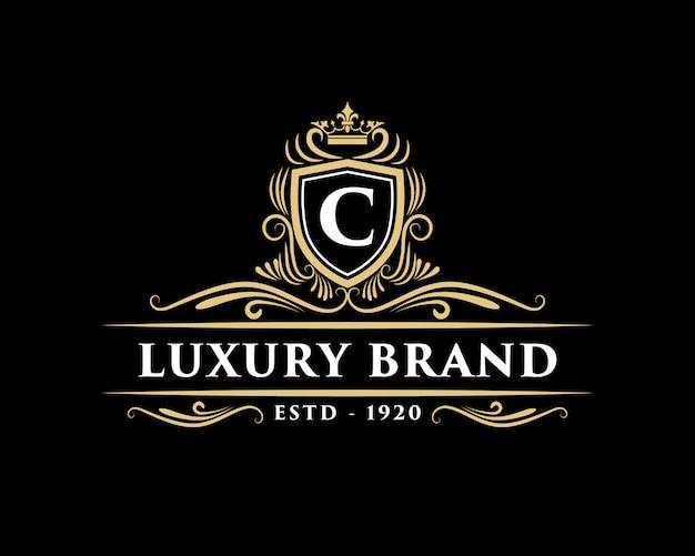 Golden calligraphic floral hand drawn monogram antique vintage style luxury logo design with crown