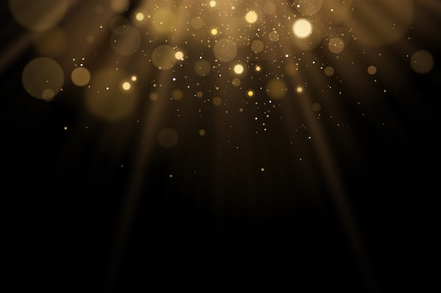 Golden flash of light with glares bokeh on a black background. rays of light with glitter.
