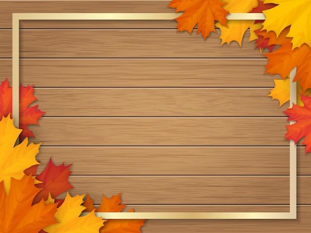 落ちたカエデの葉で飾られた金色のフレーム。木製のヴィンテージテーブルの表面の背景に紅葉。