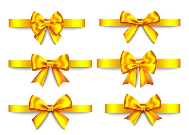 金色のギフトの弓は、白い背景で隔離を設定します。クリスマス、新年、誕生日の金の装飾。バナー、グリーティングカード、ポスターの現実的な装飾要素をベクトルします。