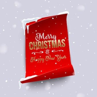 雪の中で湾曲したエッジを持つ垂直の赤い紙にゴールデンメリークリスマスと新年あけましておめでとうございますのテキスト。