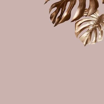 분홍색 배경에 황금 몬스테라 잎