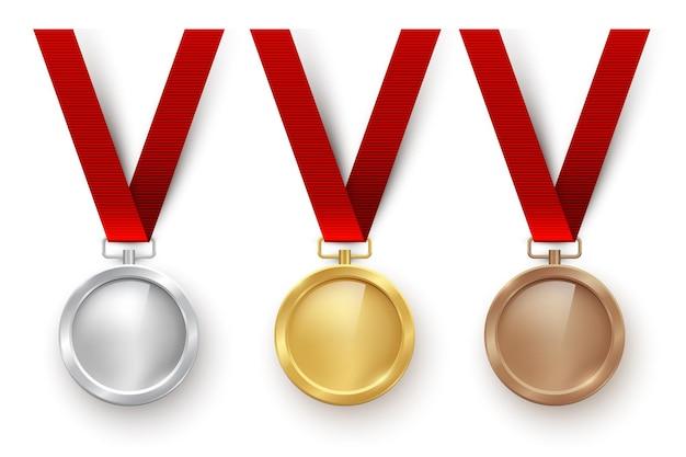 Золотые серебряные и бронзовые пустые медали, висящие на красных ленточках, изолированные на белом фоне