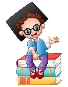 Graduation boy sitting on piles of books Premium Vector