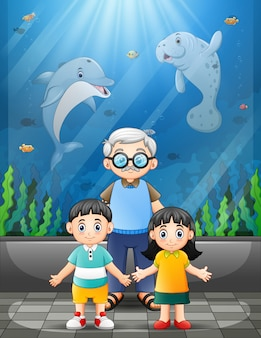 Grandfather and children watching sea animals in a giant aquarium