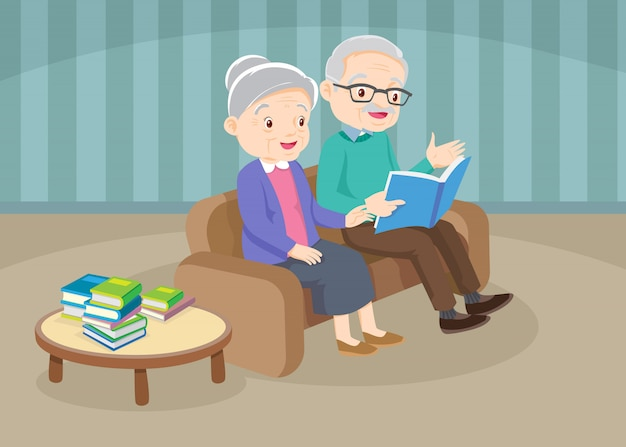 Grandfather with grandmother reading book together on sofa