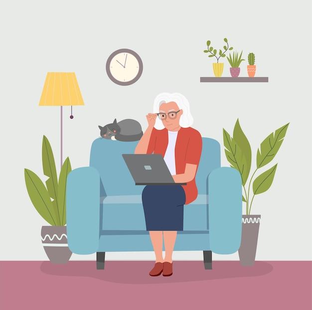 Бабушка на удобном диване и с помощью ноутбука в гостиной.
