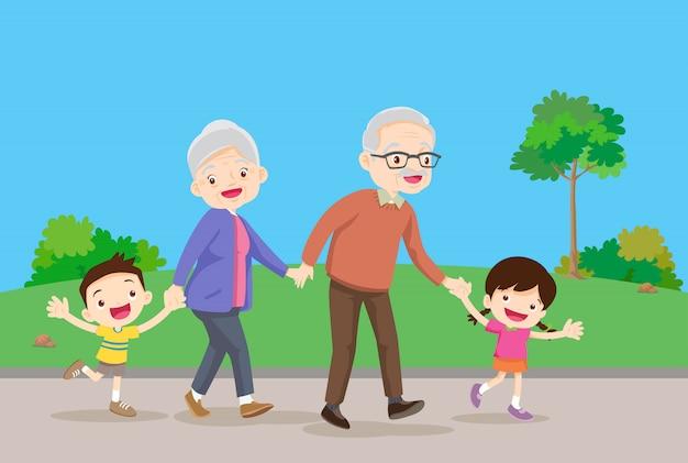 Бабушка и дедушка с детьми гуляют в парке