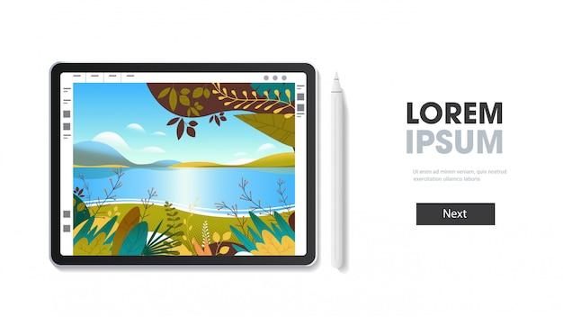 Графический планшет с красивыми пейзажными обоями на экране, изолированными на белой стене