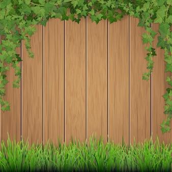 Трава и висит плющ на фоне старых деревянных досок.