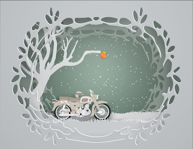 Gray motorcycle parked under dry trees in winter background