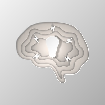 Gray silhouette of the brain carved on paper.