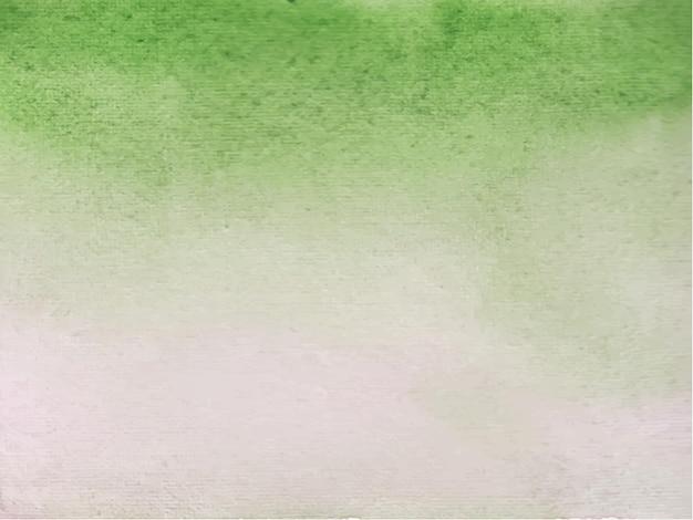 緑の抽象的な水彩画のハンドペイント。白い紙に色がはねかける