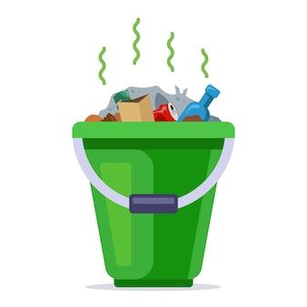 쓰레기로 채워진 녹색 양동이. 가정용 쓰레기