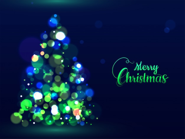 Green calligraphy text merry christmas and creative xmas tree made by bokeh effect on blue greeting card .