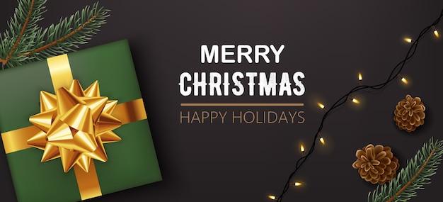 소나무 콘과 함께 황금 리본을 가진 녹색 크리스마스 선물 상자
